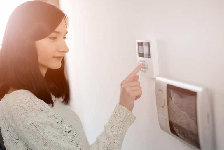 Young woman entering code on keypad of home security alarm. Video intercom next to alarm keypad.